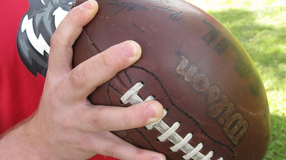 amerikkalainen jalkapallo kädessä heittoasennossa