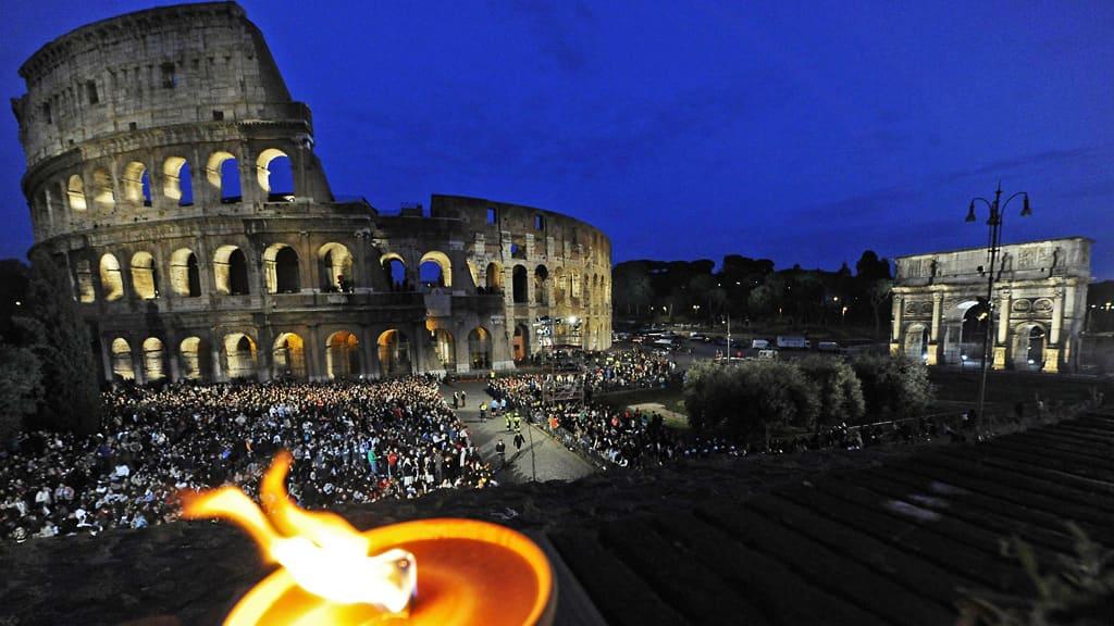 Colosseum iltavalaistuksessa ja paljon ihmisiä sen ympärillä.