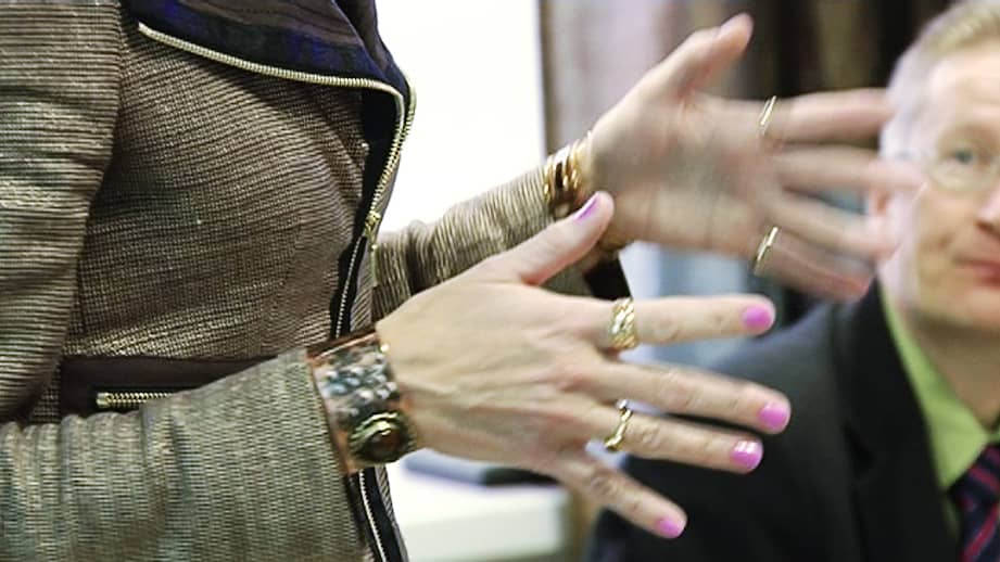 Naisjohtajan kädet liikkuvat hänen pitäessään puheenvuoroa kokouksessa.