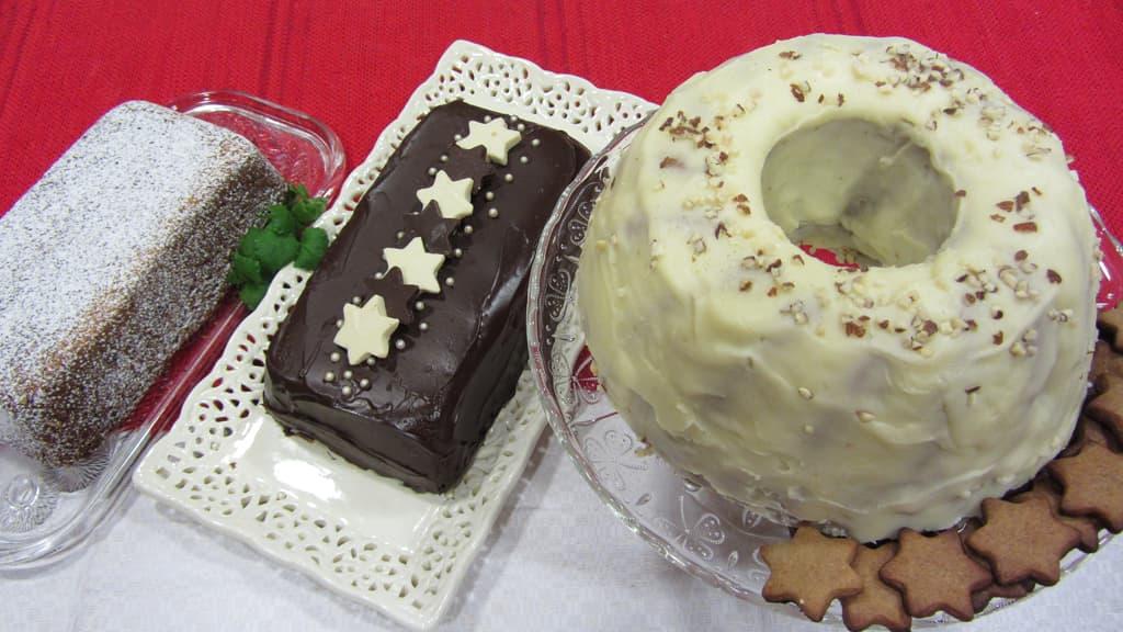 Kuvassa punaisen pöytäliinan päällä viikuna-porkkanakakku,  konjakkinen kahvi-suklaakakku ja luumu-porkkanakakku