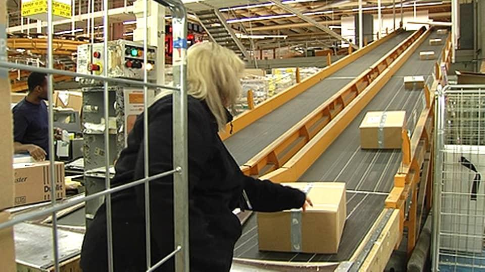 Nainen käsittelee paketteja Itellan lajittelukeskuksessa.