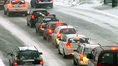 Autoja lumisessa maisemassa jonottamassa. Punaiset jarruvalot hehkuvat.