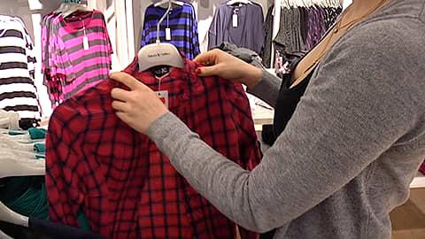 Vaatekaupan myyjä panee kauluspaitaa vaateripustimeen myymälässä.