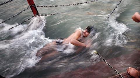 Mies kastautuu virtaavassa Ganges-joessa.