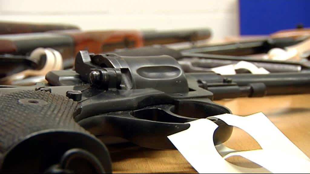 Pistooli ja muita aseita pöydällä.