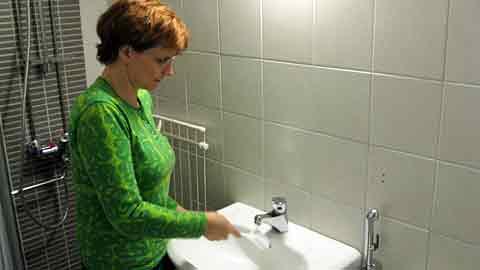 Kuvassa nainen puhdistaa käsienpesuallasta