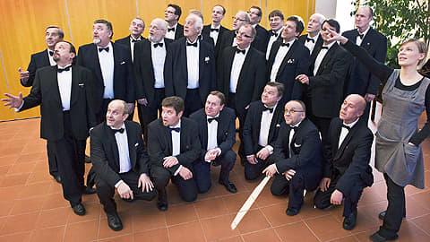 Kuvassa mieskuoro Laulu-Jaakot ja kuoronjohtaja Vuokko Heikkilä.