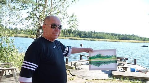 Jyrki Kangas pitää kädessään maalaamaansa taulua kesämökkinsä laiturin edessä.
