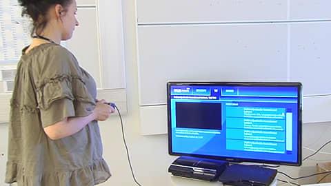 Nainen katselee Ylen Areenaa Playstation 3:n kautta.