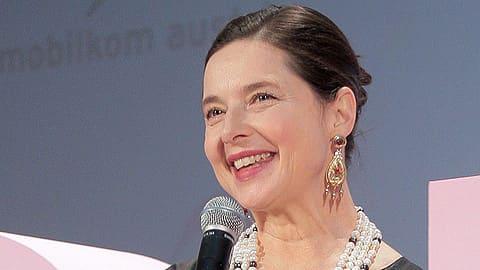 Näyttelijä Isabella Rossellini hymyilee. Mikrofoni kädessään.