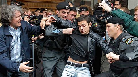 Poliisi pidättää mielenosoitukseen osallistuneen miehen.
