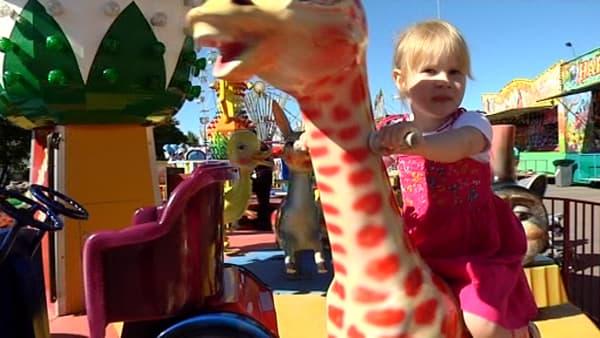 Tyttö istuu karusellissa kirahvin selässä.