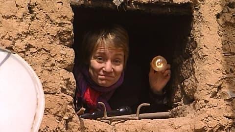 YLEn Pekingin-kirjeenvaihtaja Katri Makkonen. Kurkistaa rakennuksen ikkunasta hehkulamppu kädessään Kiinassa.