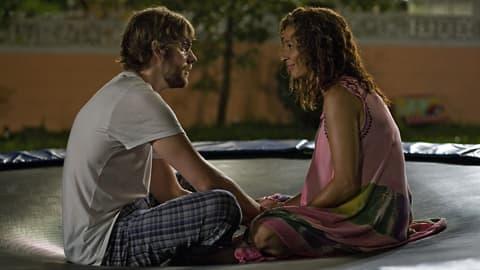 Mies ja nainen keskustelevat illan hämärässä.