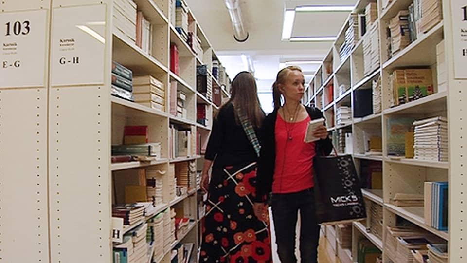 Kaksi naisopiskelijaa kirjastossa hyllyjen välissä etsimässä kirjoja.