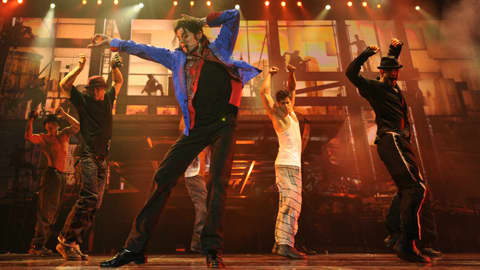 Sini-punaiseen takkiin ja mustiin housuihin pukeutunut Jakson tanssii punertavissa valoissa, taustalla neljä muuta miestanssijaa.