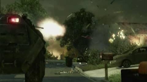 Kohtaus pelistä - panssariajoneuvosta ammutaan kadun varressa olevaa taloa