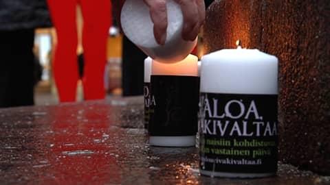 Nainen sytyttää kynttilöitä loskaisena marraskuun päivänä.