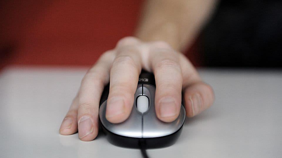 Käsi ohjaa tietokoneen hiirtä.