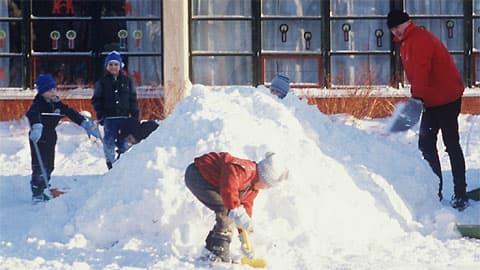 Kuvassa päiväkodin pihalla leikkiviä lapsia. Lapset kasaavat lunta, mukana puuhissa on myös yksi aikuinen.