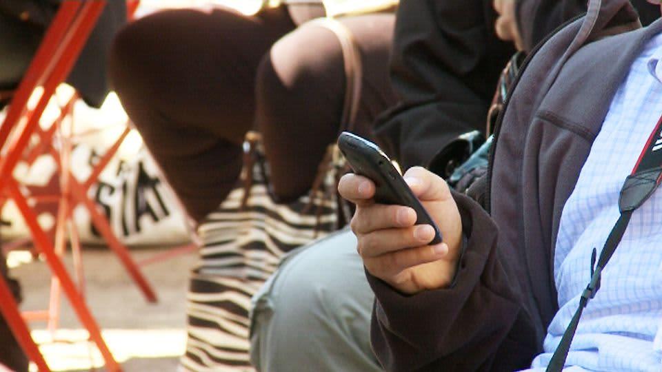 Mies näppäilee matkapuhelinta ulkona.
