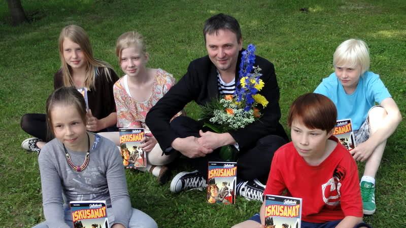 LukuVarkaus-palkinnon voittaja Tomi Kontio lapsiraadin ympäröimänä.