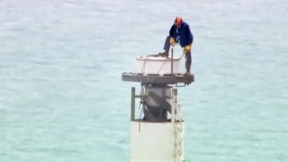 Mies seisomassa pilvenpiirtäjän antennin huipulla.