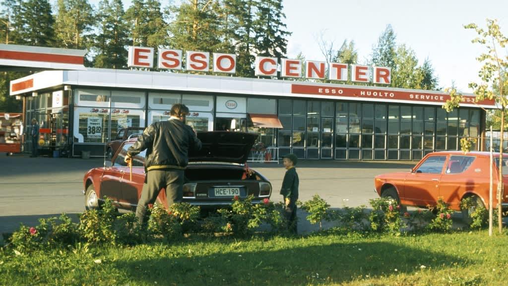 Mies ja poika Esson huoltoaseman parkkipaikalla 1970-luvulla