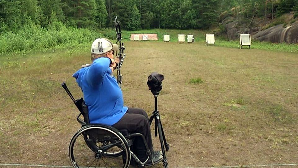 Pyörätuolissa istuva jousiampuja ampuu kohti maalitaulua.
