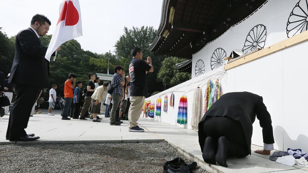 Henkilö polvistuu Yasukunin muistomerkillä Tokiossa 15. elokuuta 2012.