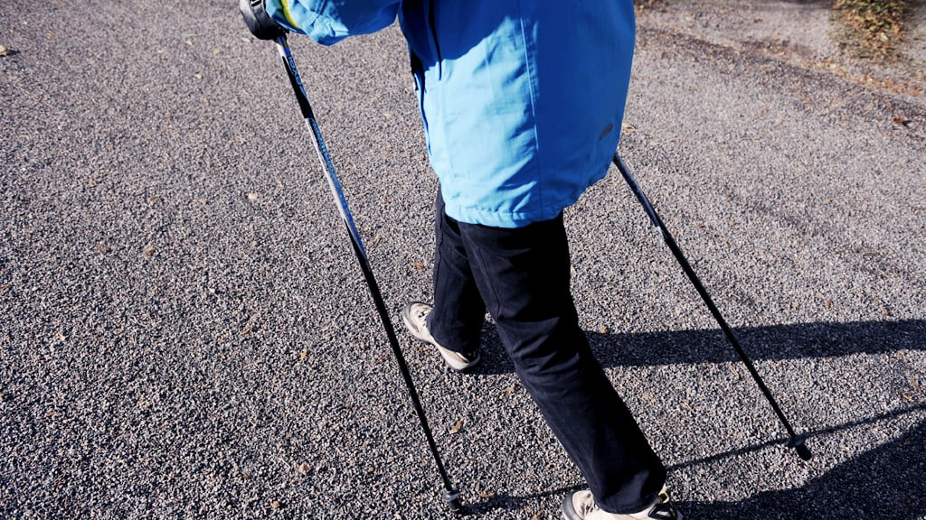 Keski-ikäinen nainen sauvakävelee.