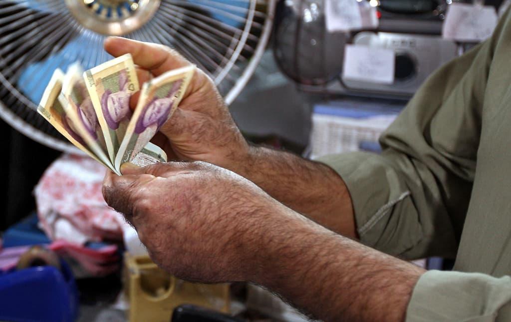 Mies laskee seteleitä käsissään. Hänellä on 50 000 Rialia.
