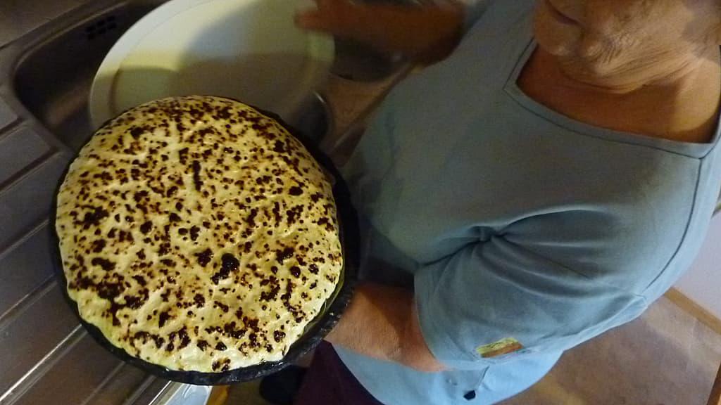 Tyyne Rautiainen nostaa valmiiksi paistuneen juustoleivän leivinuunista.