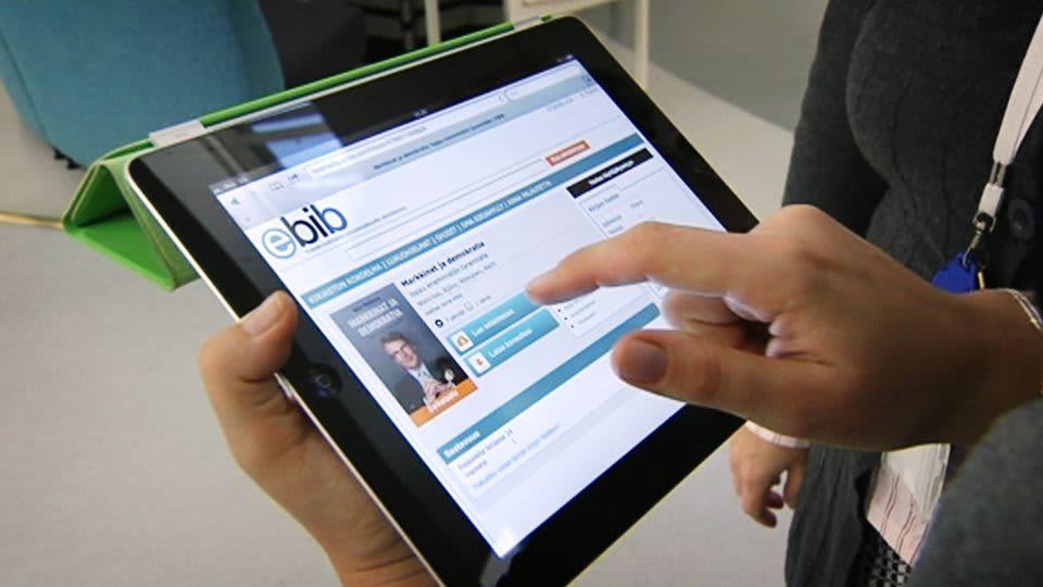 Henkilö selaa e-kirjapalvelua tabletilta.