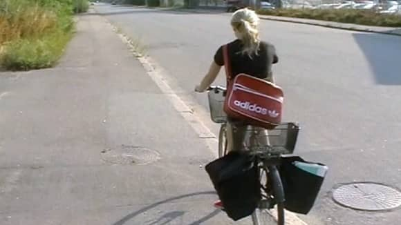 Tyttö jakamassa mainoksia pyörällä.