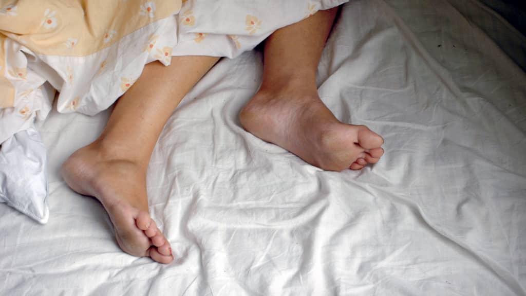 Nukkuvan naisen jalat näkyvät peiton alta.