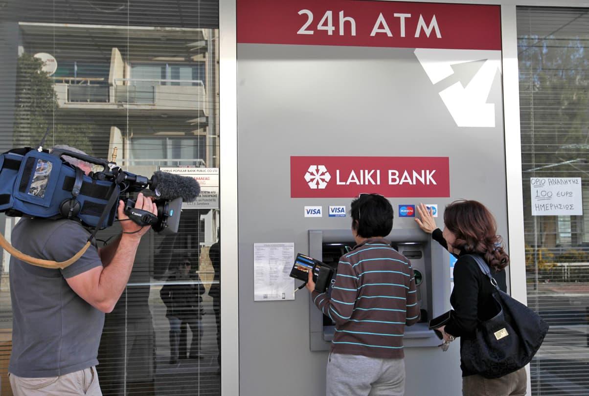 Kameramies kuvaa kun paikalliset asioivat pankkiautomaatilla Nikosiassa 26. maaliskuuta. Konttoriin pääsee vasta torstaina.