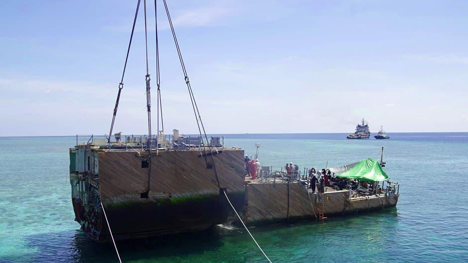 Osaa pilkotusta laivasta nostetaan merestä.