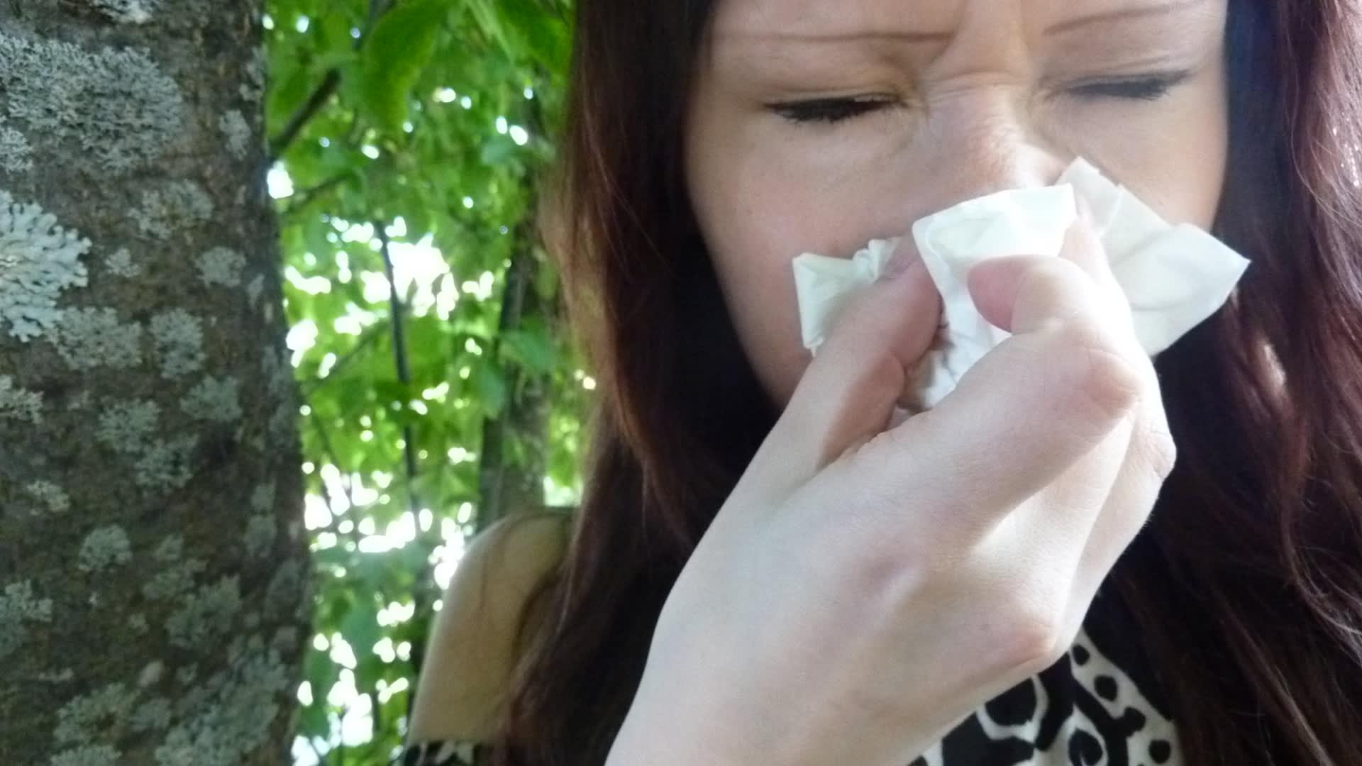 Nainen niistää nenäänsä.