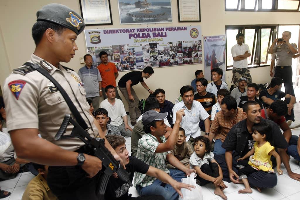 Aseistettu poliisi vartioi pakolaisjoukkoa