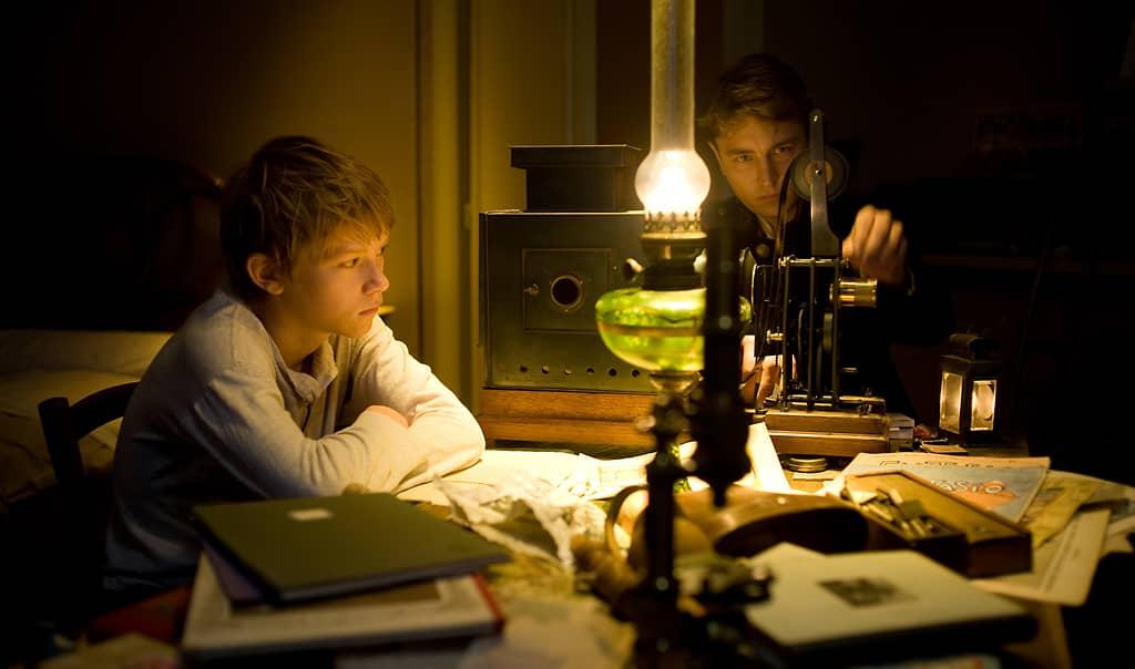 Still-kuva Renoir-elokuvasta. Kaksi poikaa virittelee taikalyhtyä.