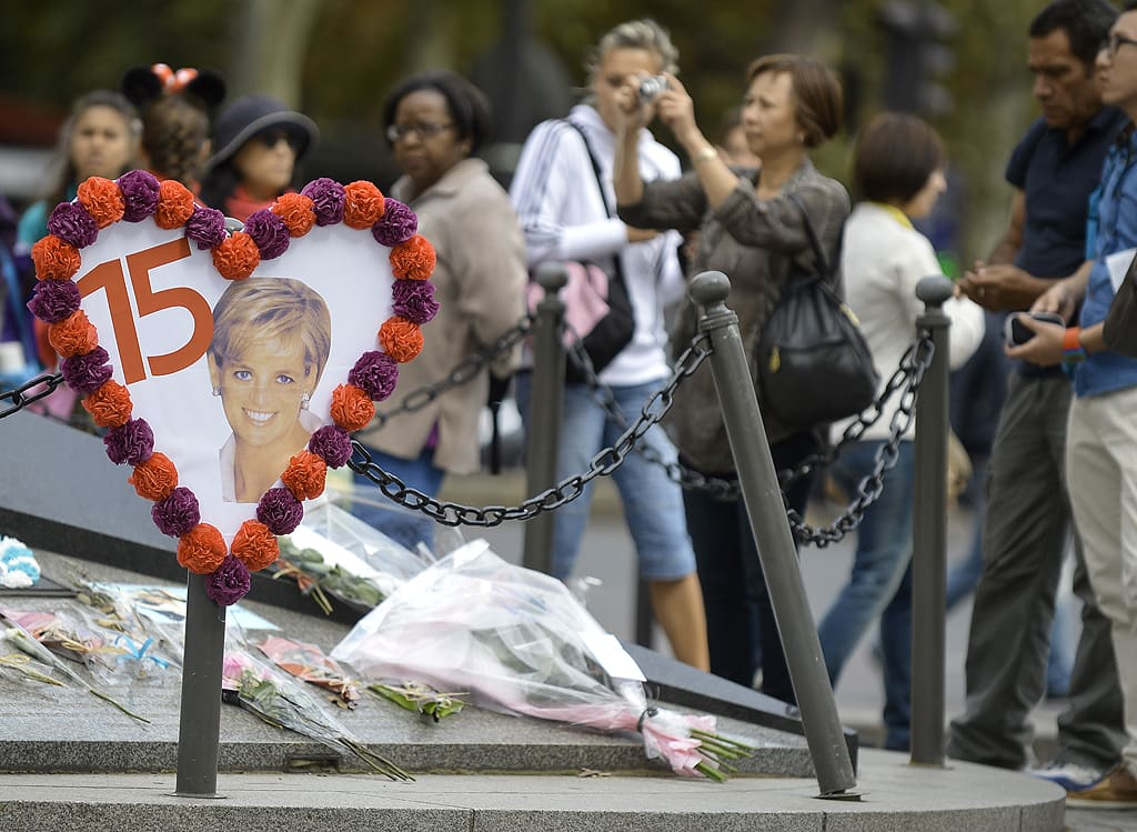 Ihmiset tuovat kukkia ja tervehdyksiä Vapauden liekki -patsaalle.