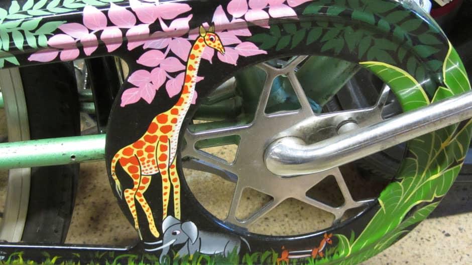 Afrikkalaisella Tinga Tinga tyylillä on maalattu kirahvi ja norsu polkupyörän kettinginsuojaan