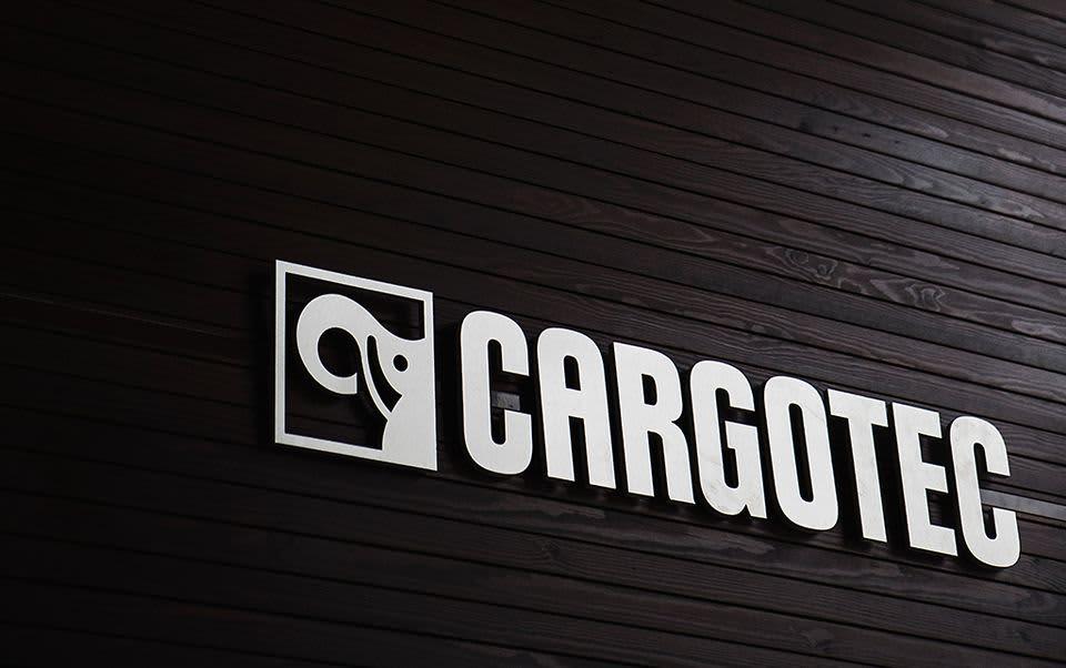 Hopeinen Cargotecin logo tummaa paneeliseinää vasten.