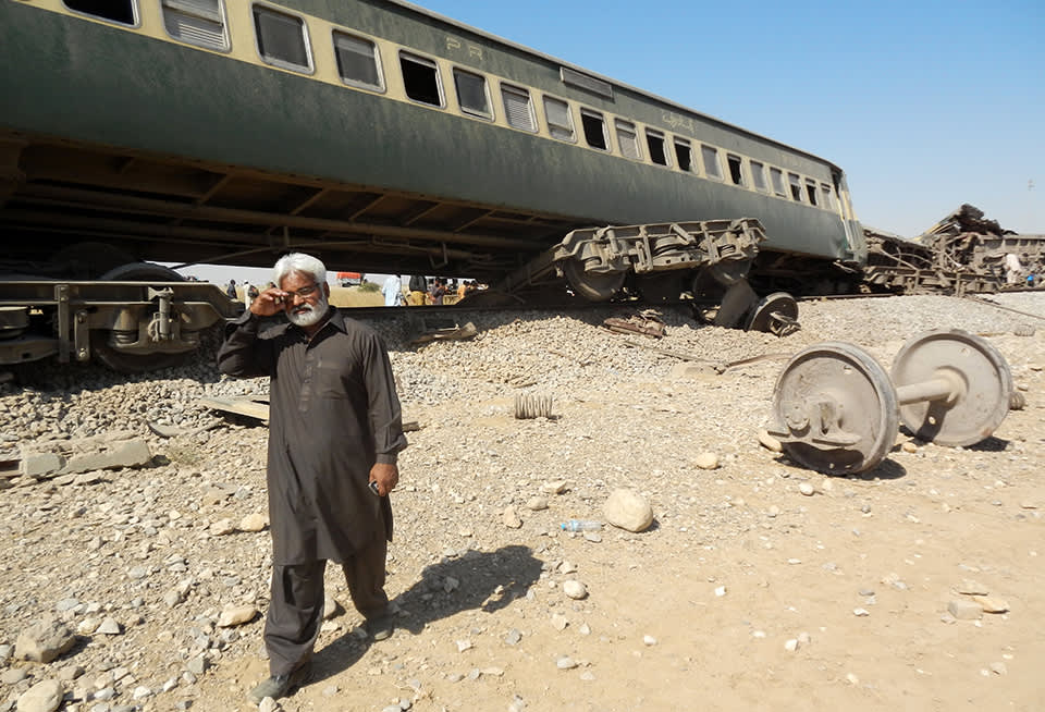 Mies kävelee romuttuneen junanvaunun vieressä.