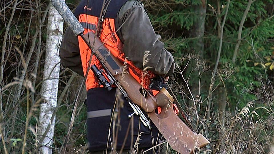 Metsästäjä ase olalla.