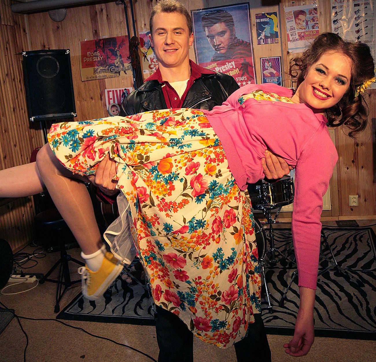 Kuvassa nuori mies sylissään nuori nainen teatterin näyttämöllä