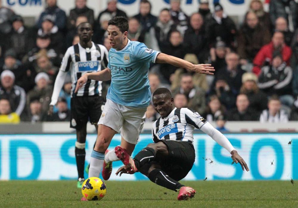 Newcastlen Mapou Yanga-Mbiwa (oik.) taklaa palloa kuljettavaa Manchester Cityn Samir Nasria (vas.).