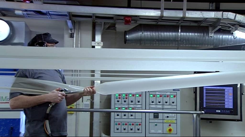 mies valmistaa tehtaassa makkarankuorta