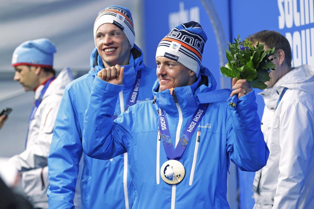 Sami Jauhojärvi tuulettaa mitali kaulassa.
